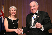 President McRobbie holds the award beside the woman who gave it to him