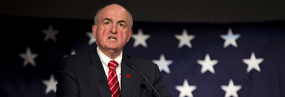 President McRobbie speaking from a podium with an American flag behind him.