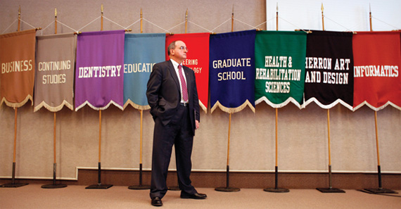 McRobbie stands in front of flags featuring school names.