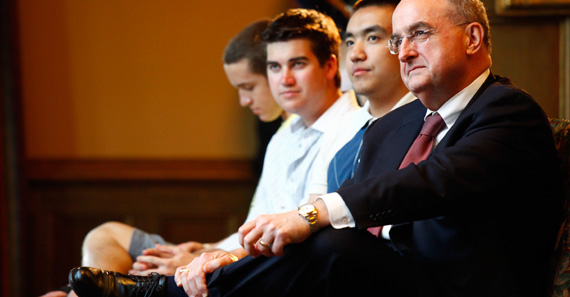 President McRobbie sits with young men.