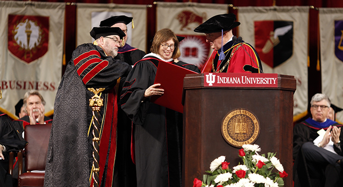 President McRobbie on stage during commencement handing the honorary degree to Linda Greenhouse