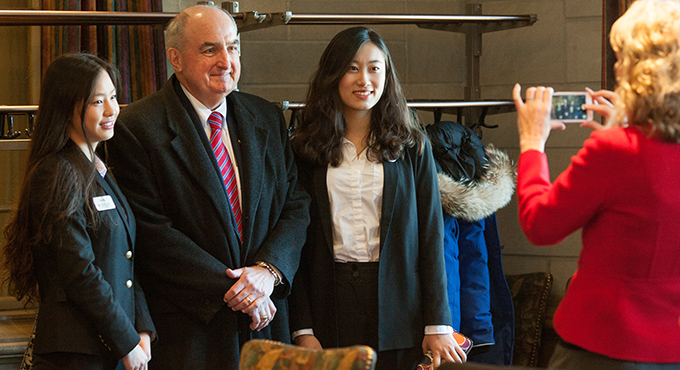 IU President Michael A. McRobbie standing with IU students Fan Bu, left, and Kejun Guo, right